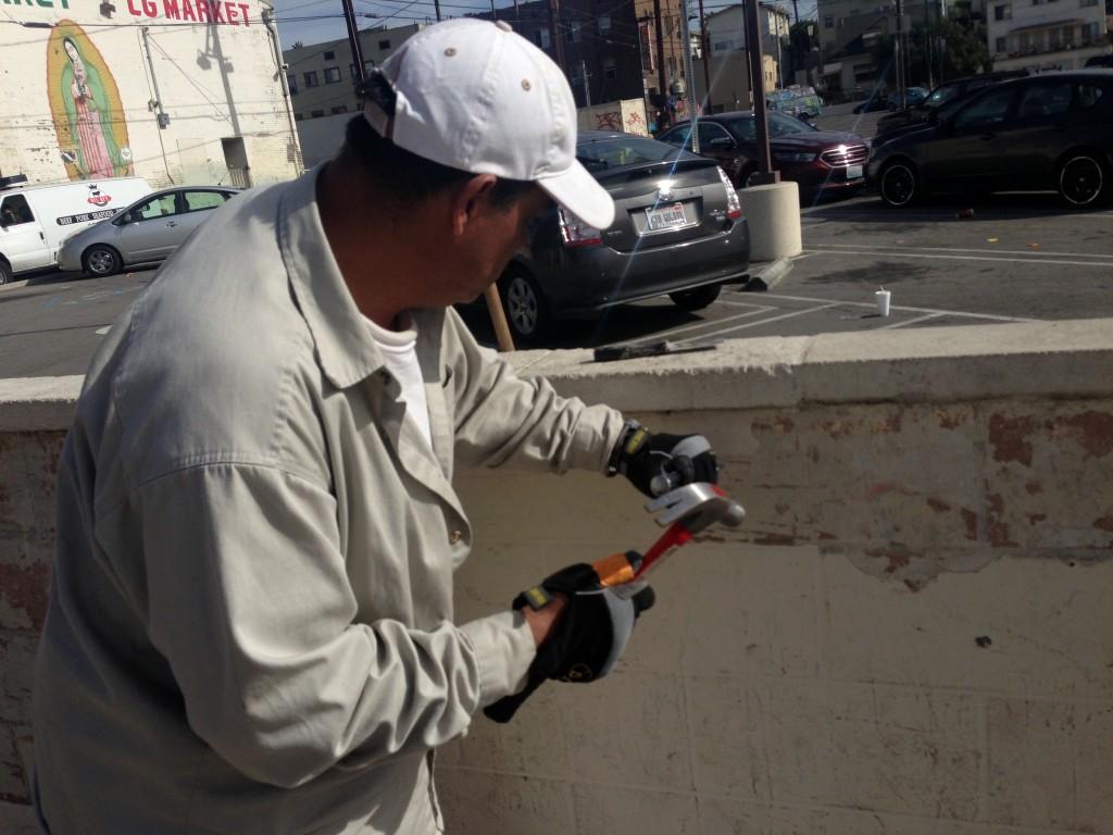 Rigo helps chip away the paint.